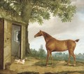 A chestnut hunter and spaniel before a stable, a church beyond - G.B. Newmarch