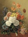 Mixed summer flowers in a glass vase on a ledge - Sara Sartorius