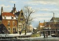 A view in a town with houses along a frozen canal, with townsfolk by a bridge - Willem Koekkoek