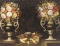 Mixed flowers in a pair of urns, bread, a jug of wine and figs on a silver dish on a ledge - (after) Tomas Hiepes