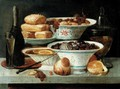 Still Life Of Porcelain Bowls Containing Sugared Dates, Grapes, And Oranges, Together With A Bottle Of Champagne, Cakes And Pickled Figs In A Glass Jar - French School