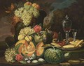 A Still Life With Grapes And Peaches In A Vase, Together With Melons, Grapes, Prunes, Peaches, Roses, Cakes And A Glass Of Red Wine On A Pewter Plate, In A Park Setting - German School